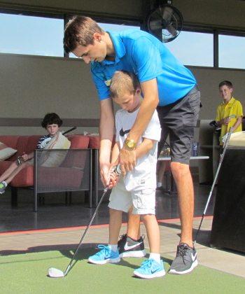 Golf ALex ? instructs Tanner Swanson (8).