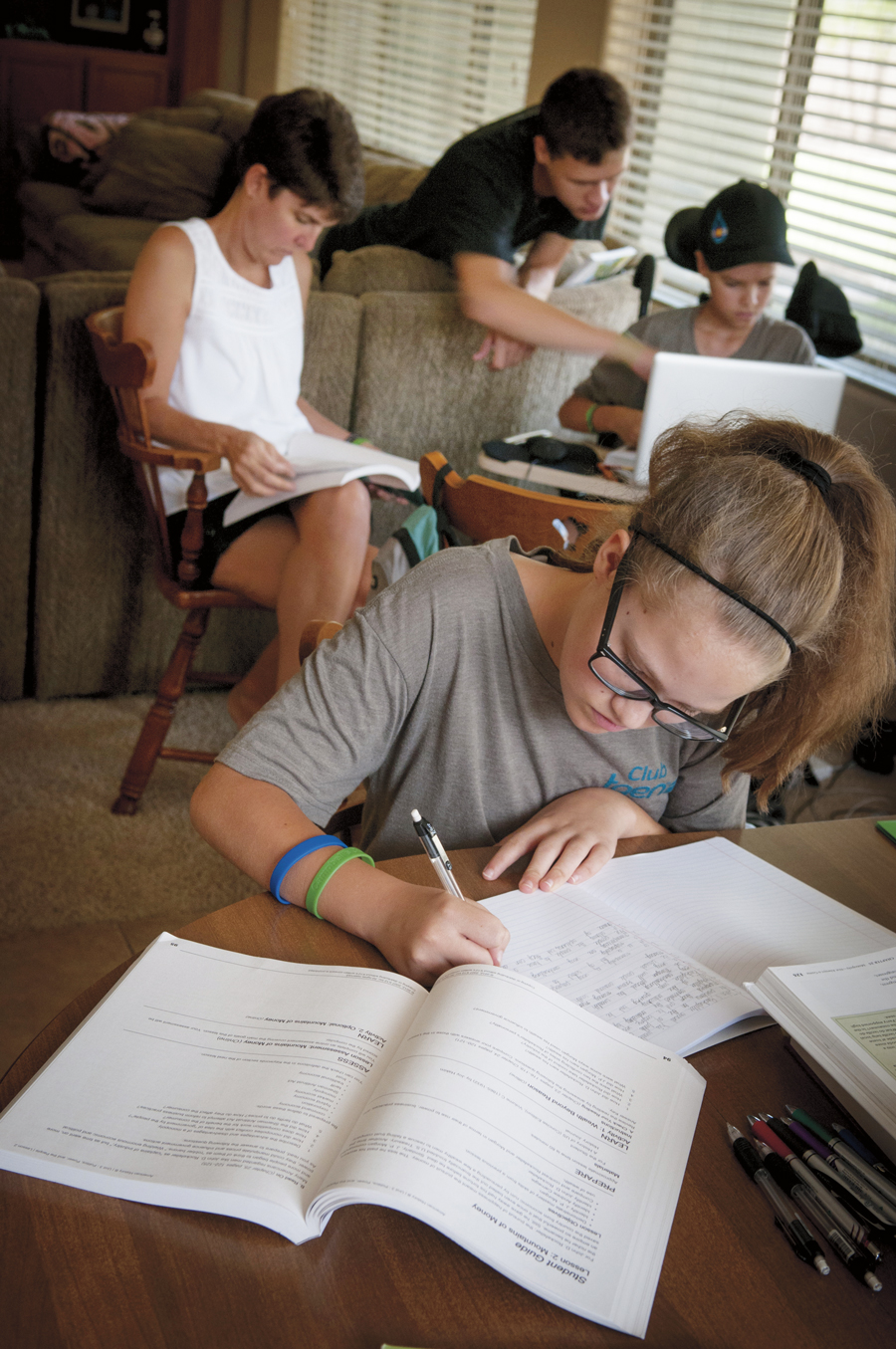 Above: Campbell Faulker (10) attends home school so his family has more flexibility around his health-care needs. Right: Campell's sister, Sage (13) works on her home-school lesson while he tackles a challenging history assignment with help from his mom, Carrie, and education coach and brother Clayton (20).