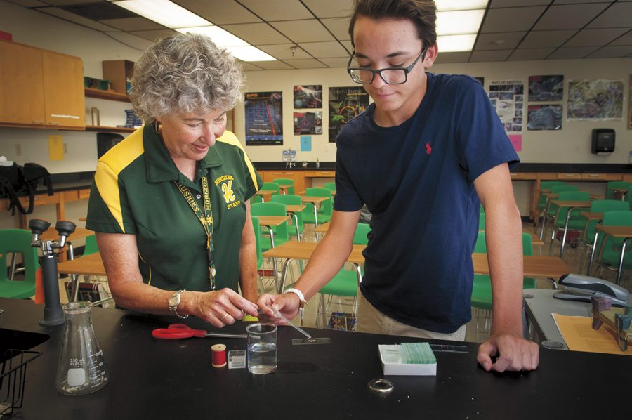Max Partridge examines a grasshopper under a microscope during an advanced biological sciences class at Horizon High School. At right, he's joined by teacher J.R. Trevas. Photos by Rick D'Elia.