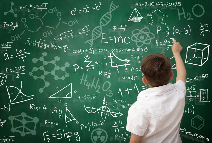 Back view of schoolboy writing math formula on green blackboard