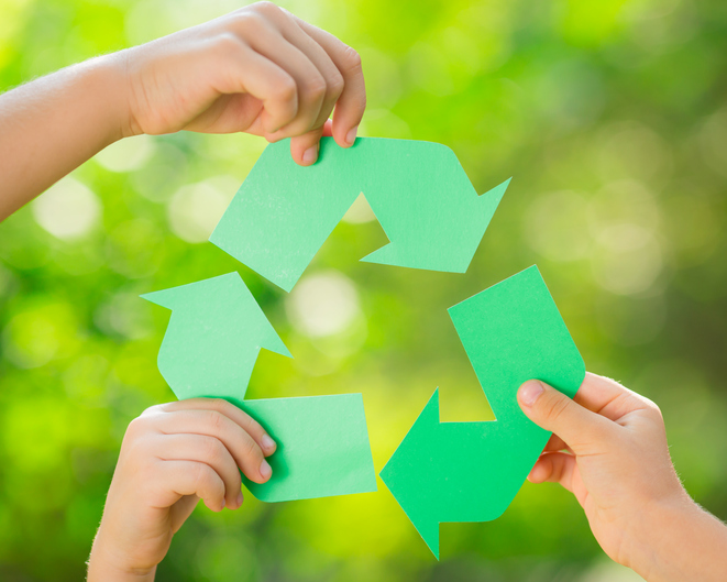 Paper RECYCLE sign in children`s hands against green spring background. Earth day concept